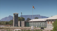 The prison on Robben Island with Table Mountain in the background Stock Footage