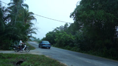 A Car And Motorcycle Passing By In Village Area, Malaysia Stock Footage