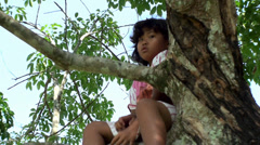 Asian girl sitting on the high tree branch. - stock footage