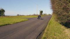 Motorcyclist with helmet walks across country road and trips over Stock Footage