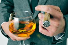 Man in suit with a cigar and a glass with brandy Stock Photos