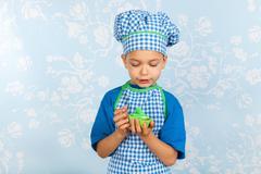 Little boy in apron baking cupcakes Stock Photos
