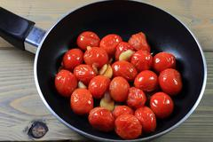 Fried with seasonings mini tomatoes in pan. Stock Photos