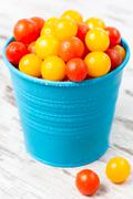 red and yellow fresh cherry tomatoes with water drops in blue bucket on woode - stock photo