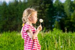 cute blonde little girl blowing a dandelion and making wish - stock photo