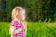 Stock Photo of pretty blonde little girl with closed eyes blowing a dandelion and making wish
