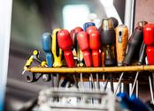 Stock Photo of assortment of tools hanging on wall. screwdrivers in mechanic garage car serv