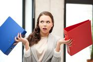 Stock Photo of unsure thinking or wondering woman with folder