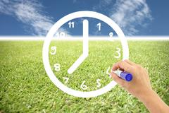hand is drawing a clock on lawns and blue sky. - stock illustration