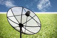 Stock Photo of satellite dish on the grass and blue sky.