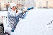 Stock Photo of attractive woman brushing snow from the car windshield