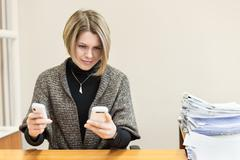 busy woman trying to respond to two phone calls - stock photo