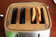 Toast in toaster in simple breakfast setting. Stock Photos