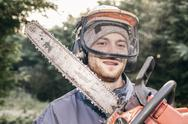 Stock Photo of professional gardener with chainsaw