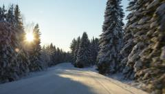 Driving through a snow-covered forest on a sunny day Stock Footage