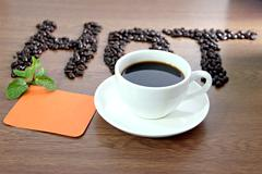 Stock Photo of white coffee cup and paper note orange lettering that hot.