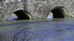River flowing high under old stone bridge arches in country Stock Footage
