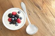 Stock Photo of assorted fresh berries with creamy yogurt