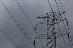Time lapse of dark and stormy clouds moving past a power transmission pylon Stock Footage