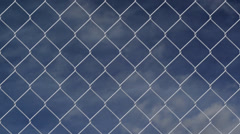 Wire fence against cloudy sky timelapse Stock Footage