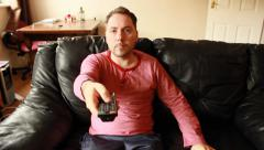 Guy sitting on the leather sofa, changing channels by using control remote. Stock Footage