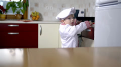 Clumsy little cook loses some cookies while carrying - stock footage