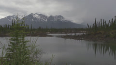 Stock Video Footage of Alaska Icy Lake and Forest Slow Pan Stormy Mountains Rainclouds