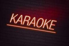 red neon sign with karaoke text on wall - stock illustration