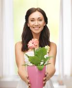 lovely housewife with flower in pot - stock photo