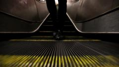 Feet walking backwards at the foot of an escalator Stock Footage