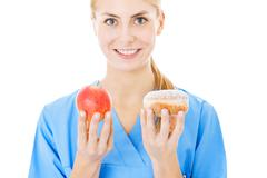 nurse holding sweet food and apple over white background - stock photo