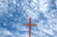 Stock Photo of wooden cross against blue cloudy sky background