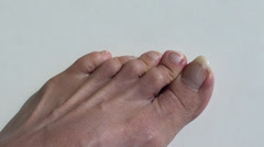 Long nails on toes against white background Stock Footage