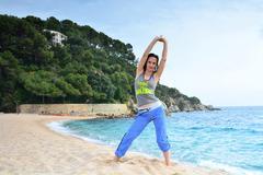 Woman doing fitness exercise on a beach Stock Photos
