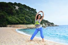 Woman doing fitness exercise on a beach - stock photo