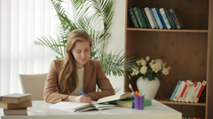 Pretty girl sitting at desk with books writing in workbook looking at camera  Stock Footage