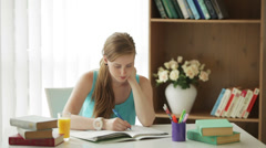 Charming girl sitting at desk writing in workbook drinking juice looking  Stock Footage