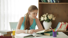 Cheerful girl sitting at desk writing in workbook looking at camera and smiling Stock Footage