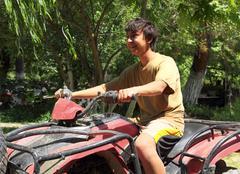 happy asian boy on quad bike atv - stock photo