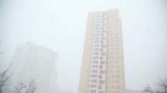 Obscure shape of a modern high-rise buildings in the snowfall - stock footage
