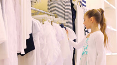 The girl chooses clothes in shop, looks through hangers Stock Footage