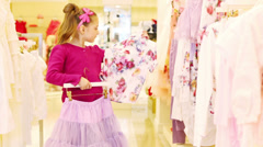 Little girl chooses an outfit of a blouse and skirt in store Stock Footage