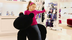 Little girl playing with a large soft toy in a clothing store Stock Footage