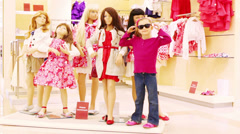 Girl stands next to mannequins in clothing store and imitate it Stock Footage