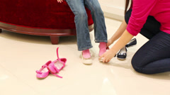 Mother helps her daughter to choose a pair of shoes Stock Footage