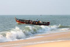 fishermen unload fresh catch of fish on beach - stock photo