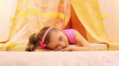 Little girl with a tail lies on the floor under canopy Stock Footage