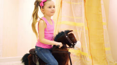 Girl in jeans and t-shirt swinging on brown rocking horse Stock Footage