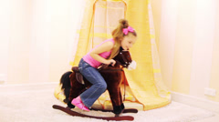 Girl swinging on rocking horse and pinch it by hitting rump Stock Footage