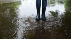 Kid have fun in puddle after rain. Legs in rubber boots splash Stock Footage